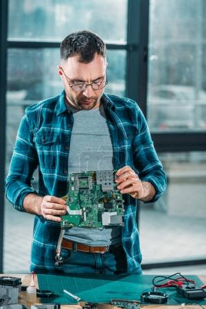 Hardware engineer checking circuit board