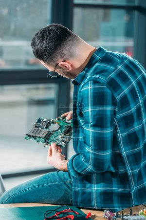 Rear view of engineer looking at circuit board