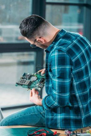 Photo pour Vue arrière d'ingénieur en regardant la carte de circuit imprimé - image libre de droit