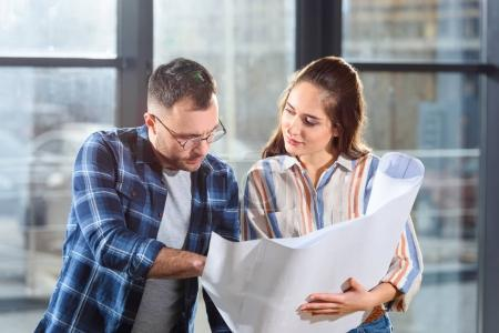 Photo for Female and male engineers looking at blueprint and discussing project - Royalty Free Image