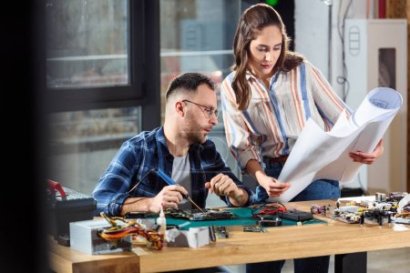 Photo for Woman and man engineers looking at hardware blueprint - Royalty Free Image