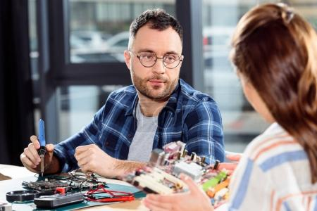 Woman holding circuit board while engineer soldering computer parts