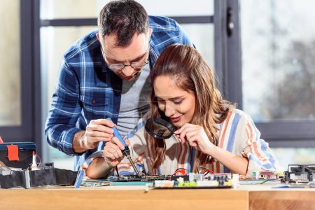 Female and male engineers soldering circuit board