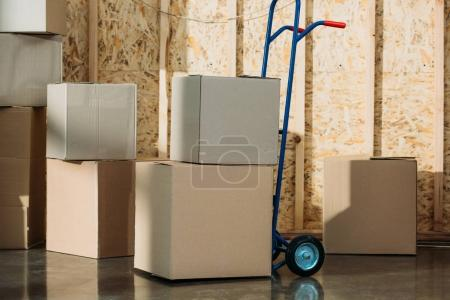 Photo for Cardboard packages and delivery cart in warehouse room - Royalty Free Image