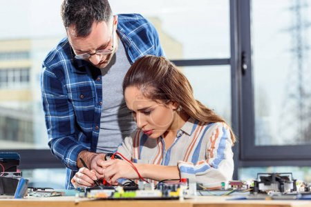 Woman and man engineers testing circuit board