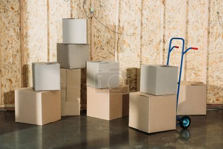 Cardboard boxes and hand truck in warehouse room