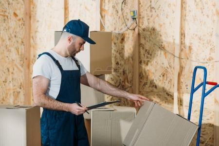 Delivery man comparing cardboard boxes and cargo declaration