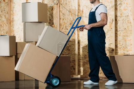 Photo for Delivery man carrying boxes on hand truck - Royalty Free Image