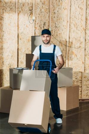 Delivery man carrying boxes on cart