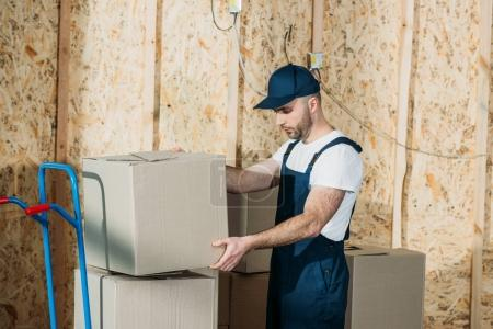Delivery man stacking boxes on cart