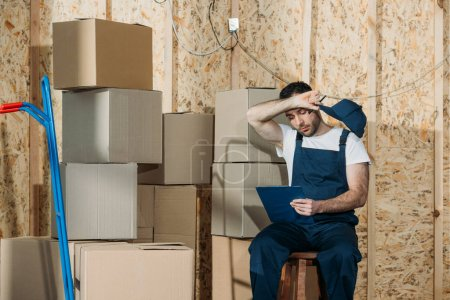 Tired loader man filling checklist while sitting by boxes