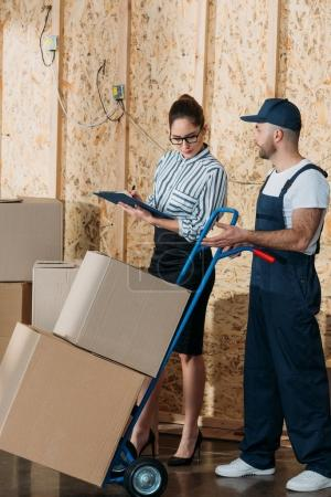 Businesswoman filling checklist while loader man carrying delivery cart
