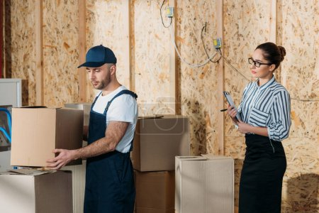 Businesswoman looking at delivery man stacking boxes