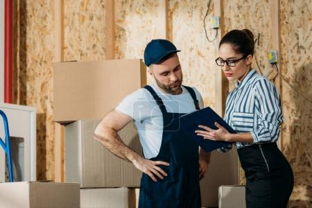 Delivery man and businesswoman looking clipboard by stacks of boxes
