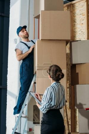 Businesswoman filling checklist while loader man standing on a ladder