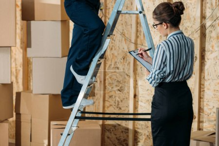 Businesswoman writing in clipboard while loader man standing on a ladder