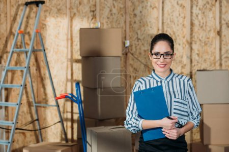 Smiling businesswoman holding clipboard standing near cargo boxes