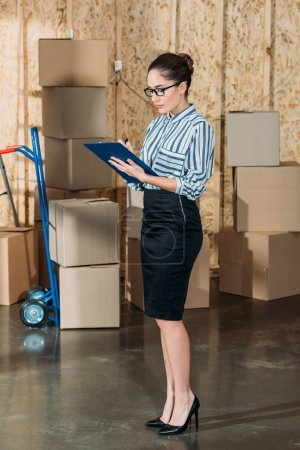 Young businesswoman writing in clipboard by stacks of delivery boxes