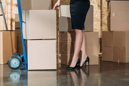 Close-up view of businesswoman standing by stack of cardboard boxes
