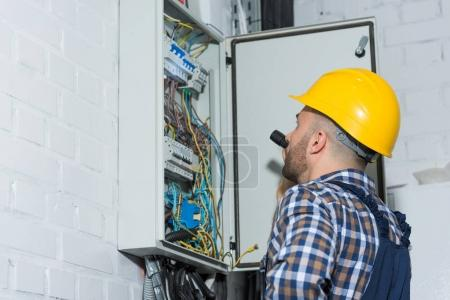 Photo for Professional electrician with flashlight working by distributor box - Royalty Free Image