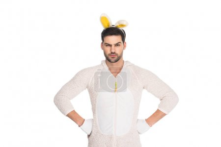 Man in rabbit costume shutting one eye and holding arms on thighs isolated on white, easter concept