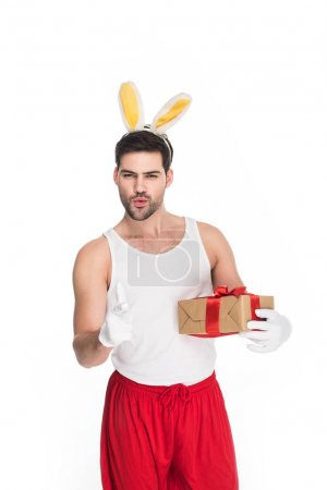 Smiling man pointing by finger and holding gift box isolated on white, easter concept