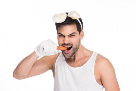 Man with bunny ears biting carrot isolated on white, easter concept