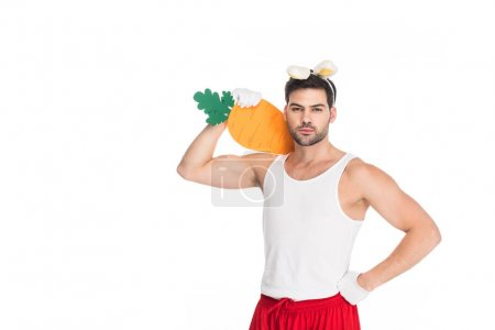 Man with bunny ears holding big carrot on shoulder isolated on white, easter concept
