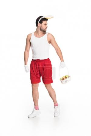 Man with bunny ears carrying basket of fruits isolated on white, easter concept