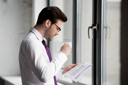 Photo for Side view of businessman with cup of coffee and newspaper - Royalty Free Image