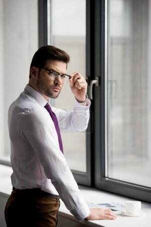 Businessman in glasses looking at camera with coffee cup and newspaper on window sill