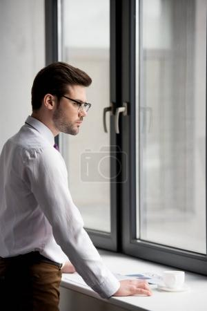 Profile of businessman in glasses with coffee cup and newspaper on window sill
