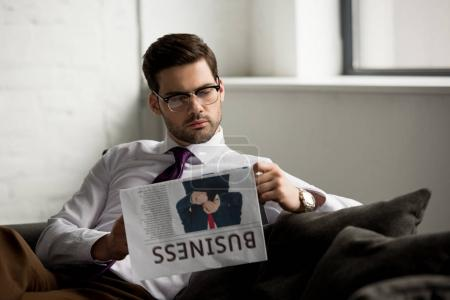 Geschäftsmann sitzt auf Couch und liest Zeitung