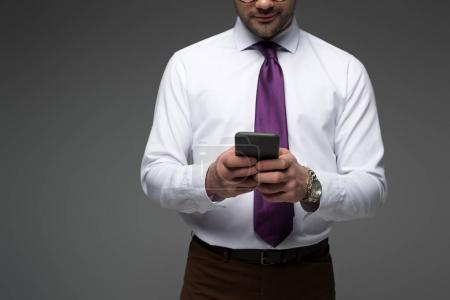 Cropped view of businessman holding smartphone in hands isolated on grey