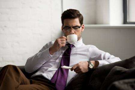 Front view of young businessman drinking coffee