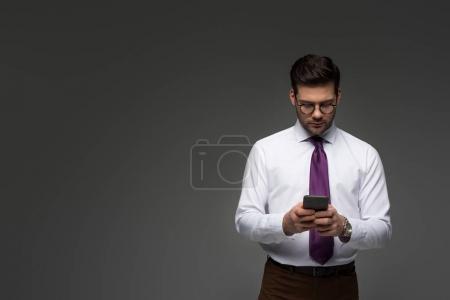 Photo pour Jeune homme d'affaires dans des verres à l'aide de smartphone isolé sur fond gris - image libre de droit