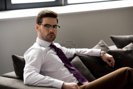Portrait of stylish businessman in glasses looking at camera