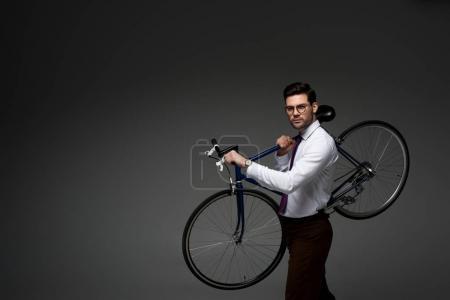 Photo pour Jeune homme d'affaires en lunettes tenant le vélo dans les mains isolées sur gris - image libre de droit