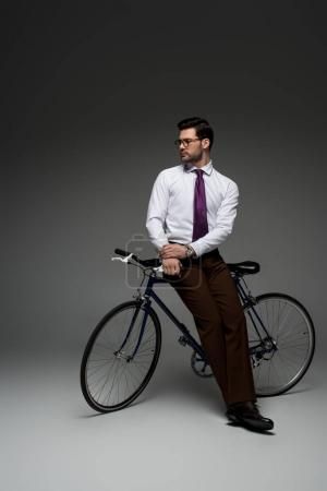Image of  stylish businessman sitting on bicycle on grey