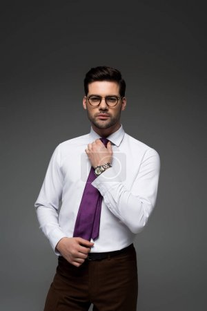 Young businessman in glasses correcting tie isolated on grey