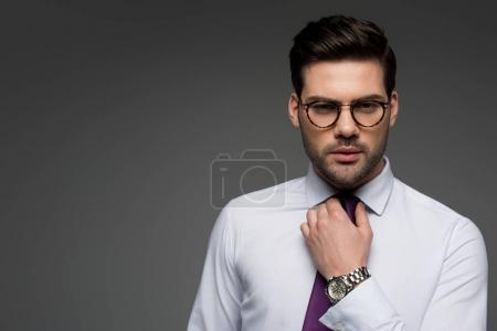 Portrait of businessman in glasses correcting tie isolated on grey