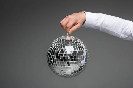 Partial view of businessman hand holding glass disco ball isolated on grey