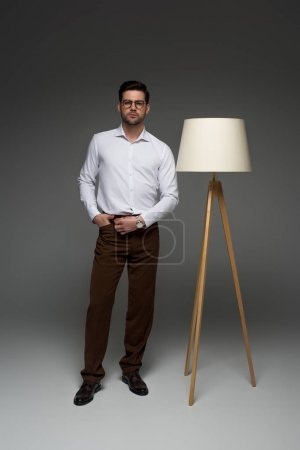 Front view of businessman standing with floor lamp beside on grey