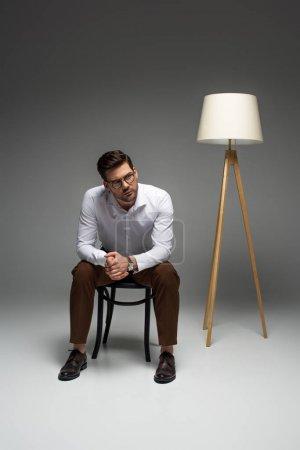 Photo pour Homme d'affaires, assis sur une chaise près de lampadaire sur fond gris - image libre de droit