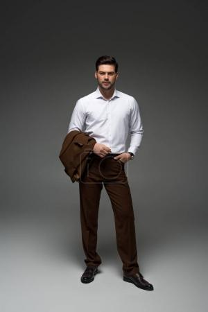 stylish businessman standing with jacket on one hand on grey