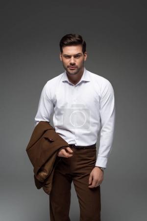 Homme d'affaires avec la veste sur debout main isolé sur fond gris