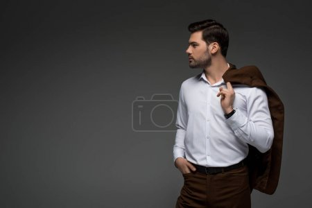 Side view of young businessman with jacket on shoulder isolated on grey