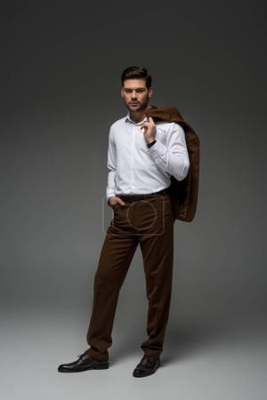 Young businessman holding jacket on shoulder on grey