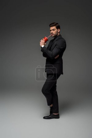 Businessman drinking from disposable cup on grey