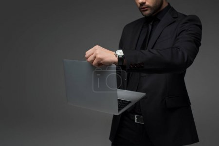 Cropped view of  stylish businessman with laptop in hands isolated on grey